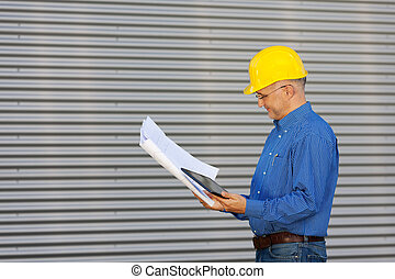 Side view of mature architect holding digital tablet while looking at blueprint against shutter