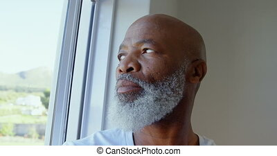 Side view of mature black man looking through window in a comfortable home 4k