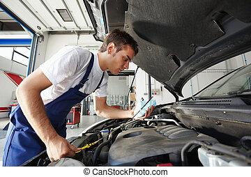 mechanic - side view of mechanic checking motor oil
