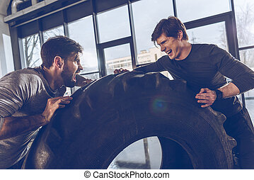 side view of men pulling tire together while exercising at the gym