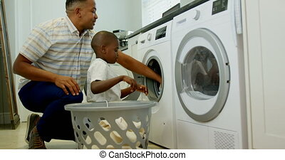 Side view of mid adult black father and son washing clothes in washing machine at comfortable home 4