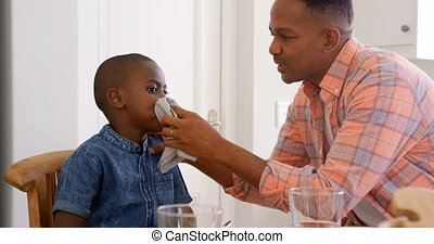 Side view of mid adult black father wiping sons mouth at dining table in a comfortable home 4k