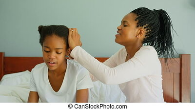 Side view of mid adult black mother dressing daughters hair ...