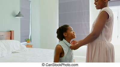 Side view of mid adult black mother helping her daughter in ...