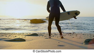 Side view of mid-adult caucasian male surfer placing ...