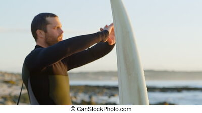 Side view of mid-adult caucasian male surfer stretching and ...