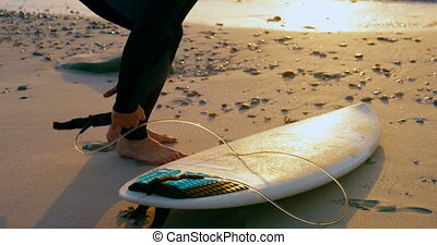 Side view of mid-adult caucasian male surfer tying surfboard...