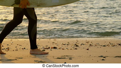 Side view of mid-adult caucasian male surfer walking with ...