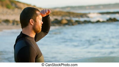Side view of mid-adult caucasian male surfer with shielding ...