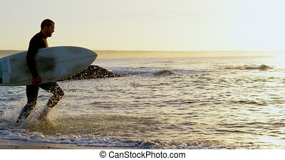Side view of mid-adult caucasian male surfer with surfboard ...