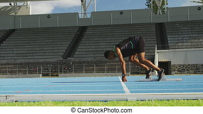 Side view of mixed race athlete preparing for race in ...