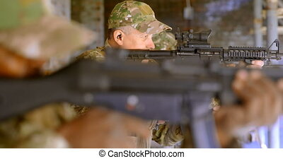 Side view of mixed-race military soldiers shooting rifle in ...
