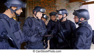 Side view of mixed-race military soldiers with rifles planing and discussing their plan at base 4k