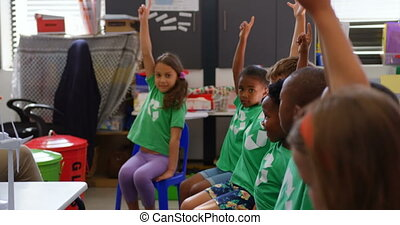 Side view of mixed-race schoolkids raising their hands in the classroom 4k