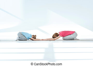 Side view of mother and daughter exercising on white performing Shashankasana Hare Pose on yoga mat