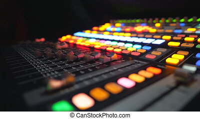 Side view of moving buttons on dj remote or soundboard. Working process in recording studio. Blurred background with brightly glow keys. Musical player at night party. Slow motion Close up