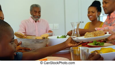 Side view of multi generation black family having food at dining table in a comfortable home 4k