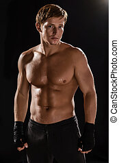 Side view of muscular man boxing on black background