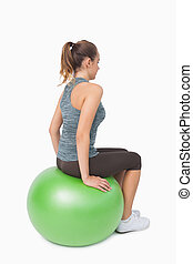 Side view of ponytailed woman sitting on fitness ball