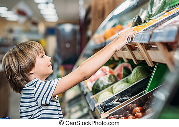boy choosing food in grocery shop