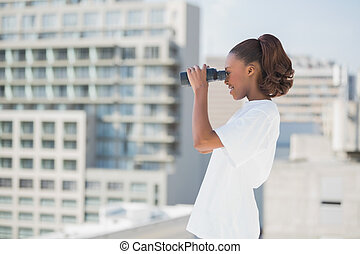 Side view of pretty woman using binoculars
