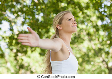 Side view of pretty young woman doing yoga spreading her arms in a park
