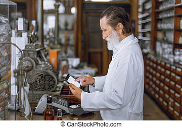 Side view of professional concentrated senior man pharmacist using digital tablet, working in ancient drugstore with vintage interior