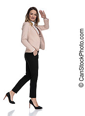side view of relaxed businesswoman walking and saluting