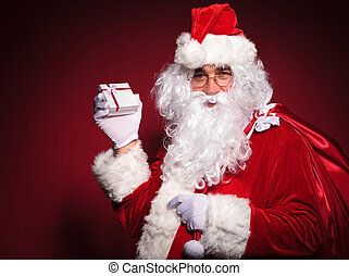 side view of santa claus holding a small present box