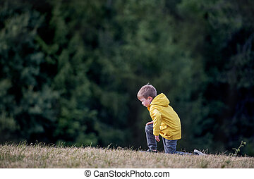 Side view of school child standing on field trip in nature, resting.