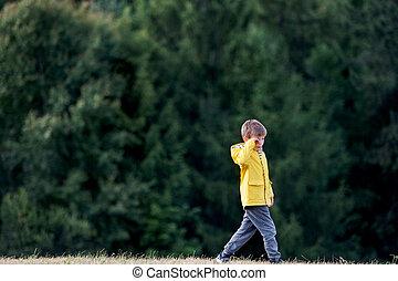 Side view of school child walking on field trip in nature, rubbing eyes.