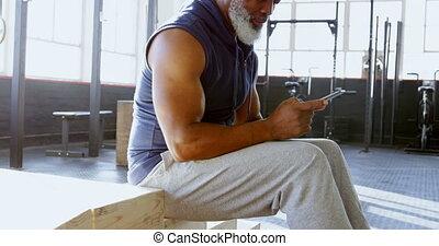 Senior man using smartphone in a gym 4k