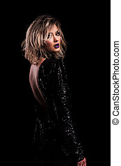 side view of sensual woman with backless black shiny dress standing on black background, looking in awe