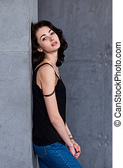 Side view of sexy blue-eyed brunette with full lips and pale complexion leaning against wall turned head to camera wearing black t-shirt and jeans
