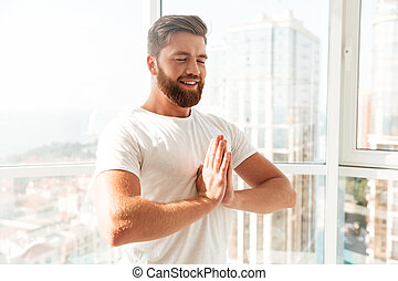 Side view of smiling bearded man meditation with closed eyes
