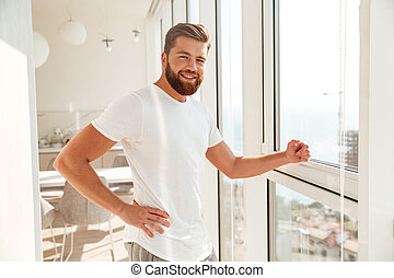 Side view of smiling bearded man standing near the window
