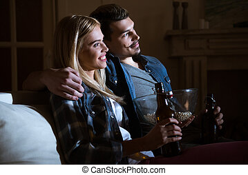 smiling couple watching movie with popcorn and beer