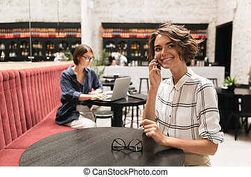 Side view of Smiling curly woman talking by the smartphone