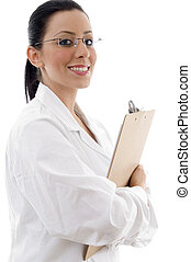 side view of smiling doctor holding writing pad against white background