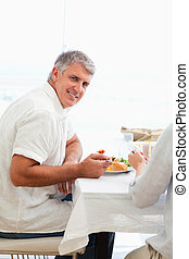 Side view of smiling man having dinner