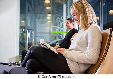 Side View Of Smiling Woman Reading Book At Airport