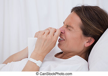 Side view of sneezing woman laying in bed