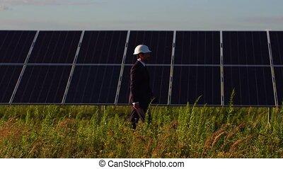 Side view of solar energy station director walking and checking photovoltaic panels.