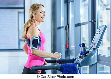 Side view of sporty blonde woman exercising on treadmill in gym