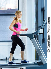 Side view of sporty blonde woman exercising on treadmill