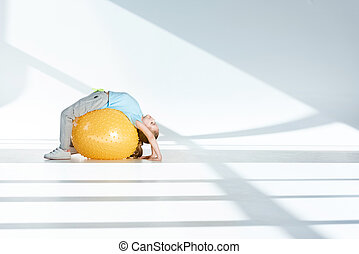 Side view of sporty little girl exercising on fitness ball