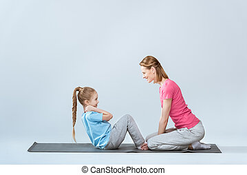 side view of sporty mother and daughter exercising on mats together on white