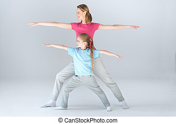Side view of sporty mother and daughter practicing warrior yoga pose together on white
