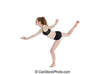 Side view of sporty woman standing on one leg - Full length...
