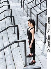 Side view of sporty young woman exercising on stadium stairs